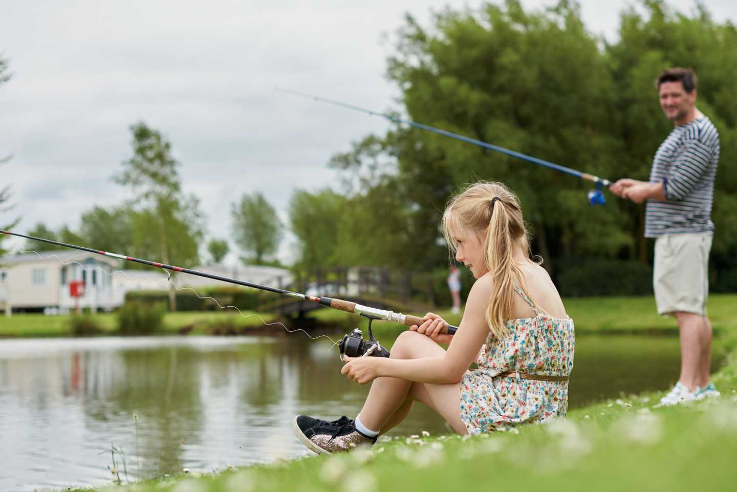 A father and daughter fishing on the bank of the coarse fishing lake