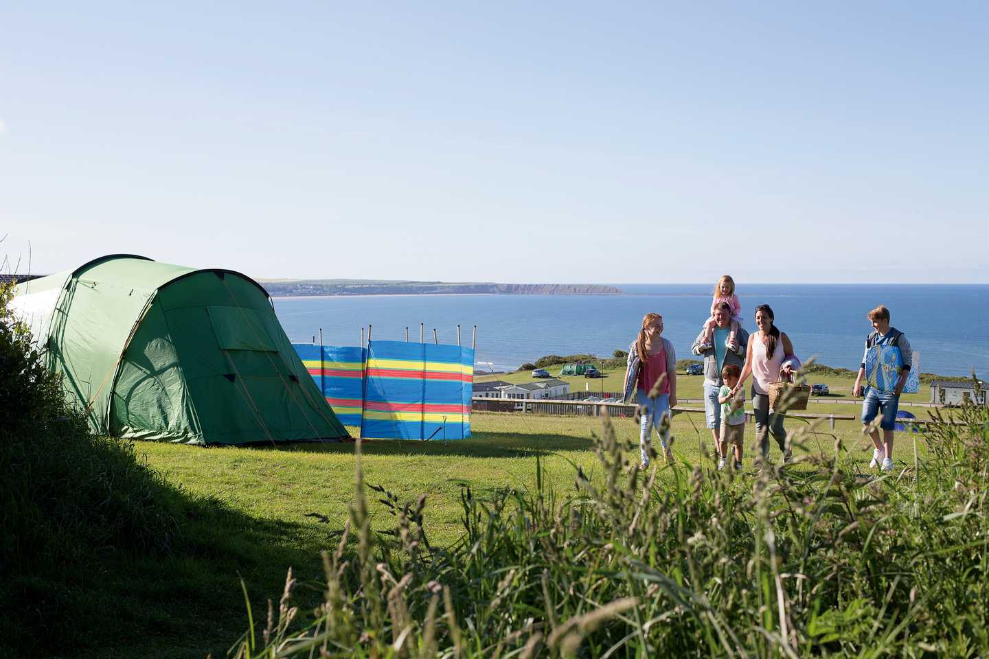 A family walking outside their tent