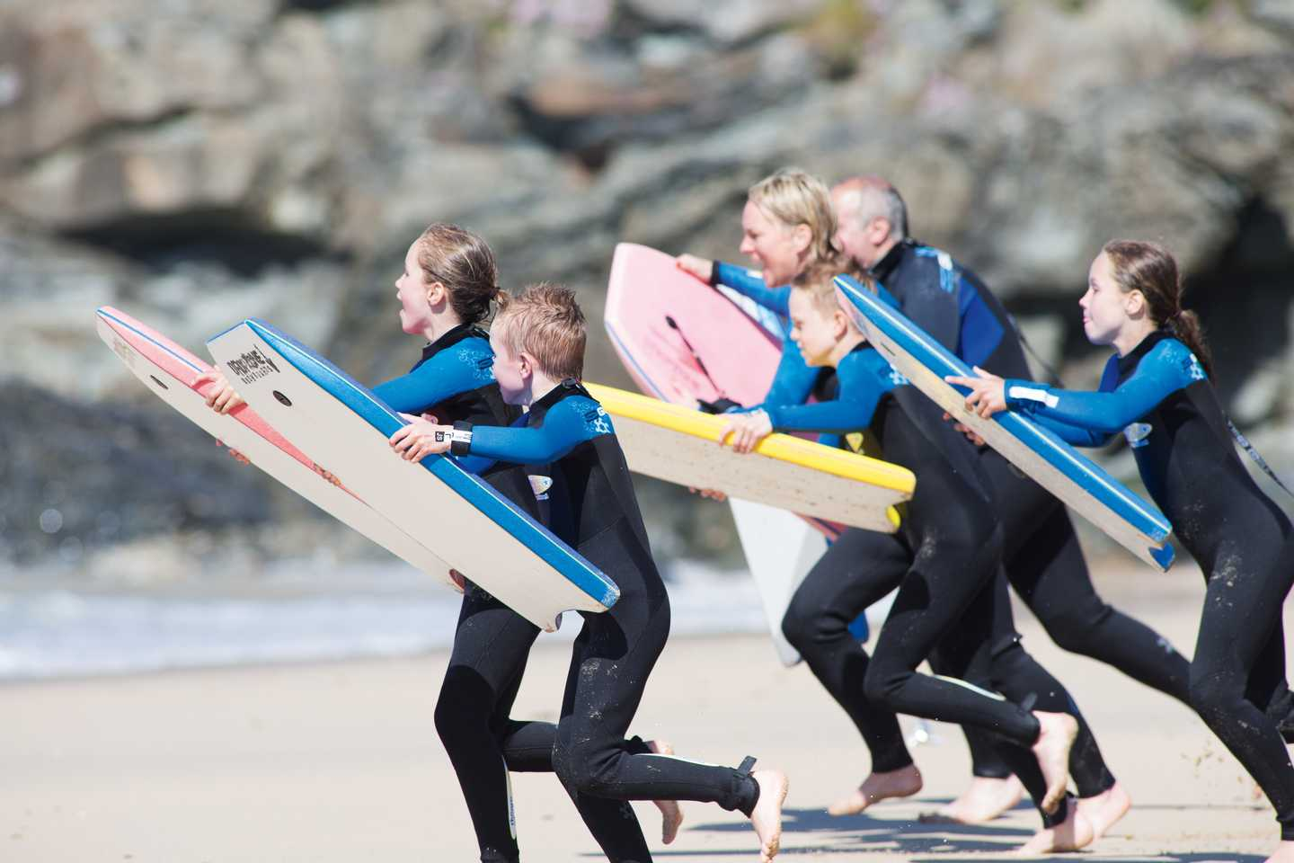 Guests running along the beach with their surf boards