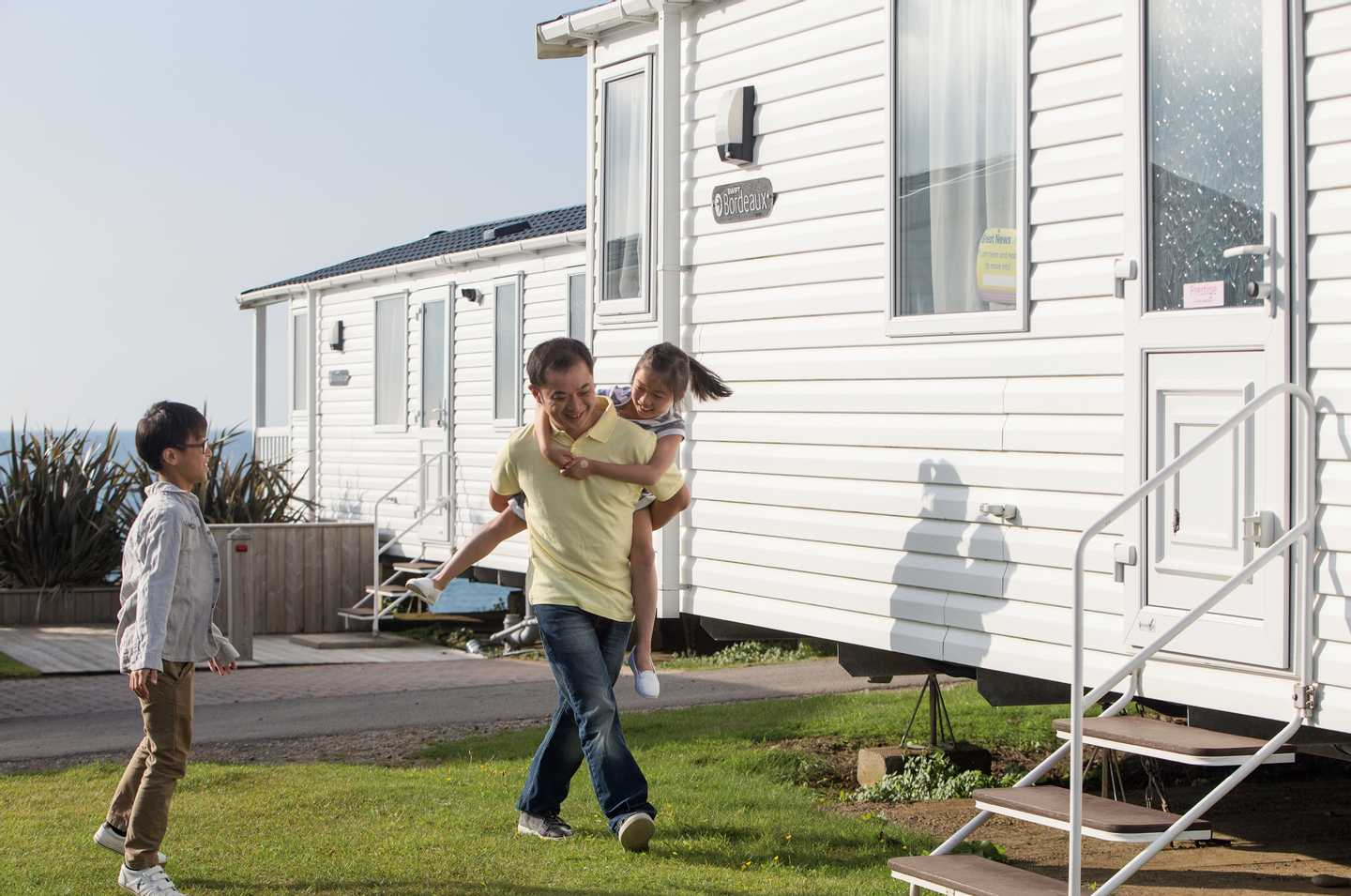 A family outside a static caravan at Riviere Sands