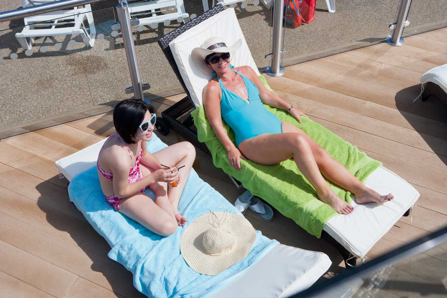 Two guests on sun loungers by the outdoor pool