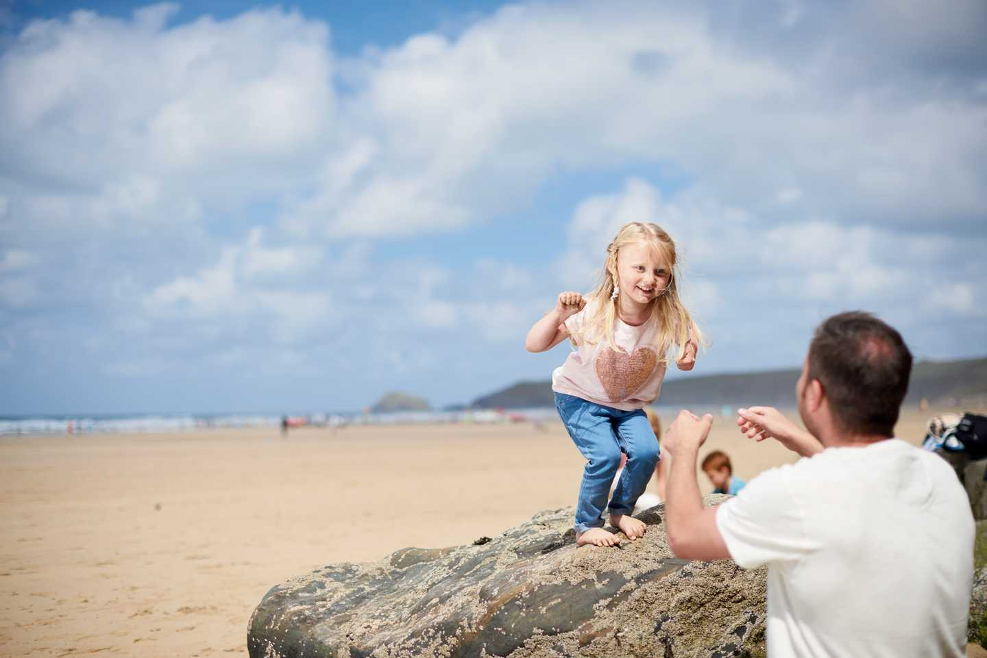 A girl jumping into her father's arms on the beach