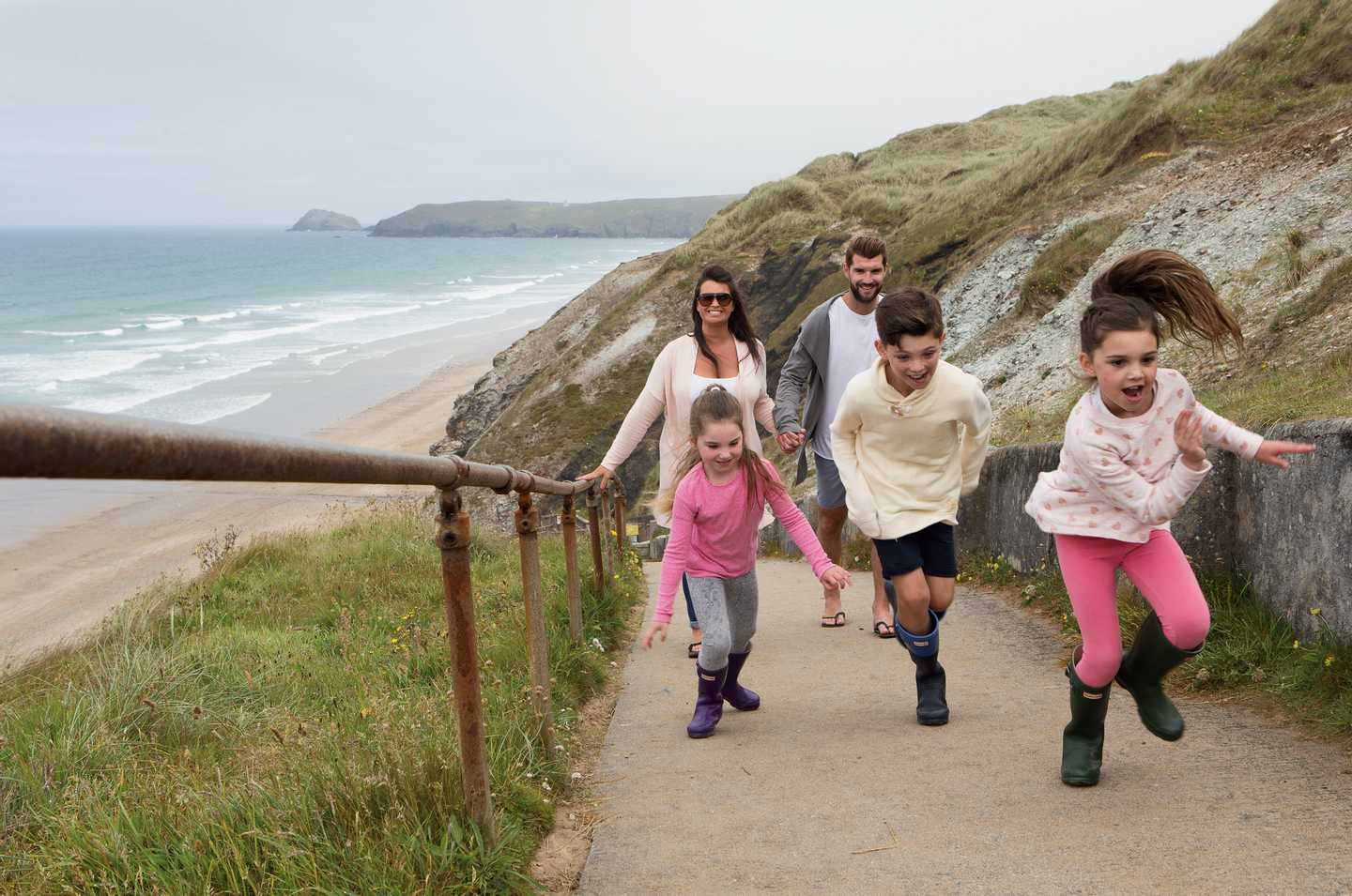 A family running up the steep pathway from the sandy beach to the park