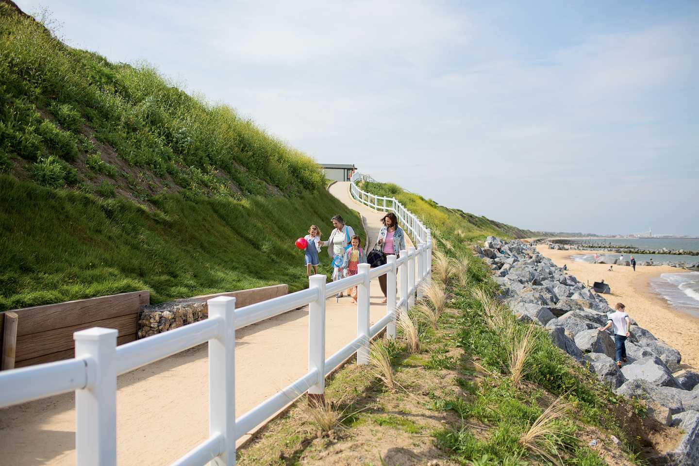 A view of the walkway between the park and the beach, the path has a white fence along the side
