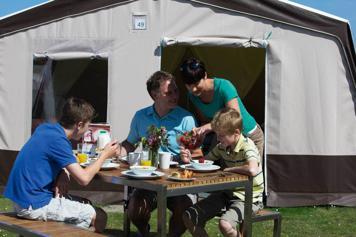 Family eating on the bench outside their Supertent at Perran Sands