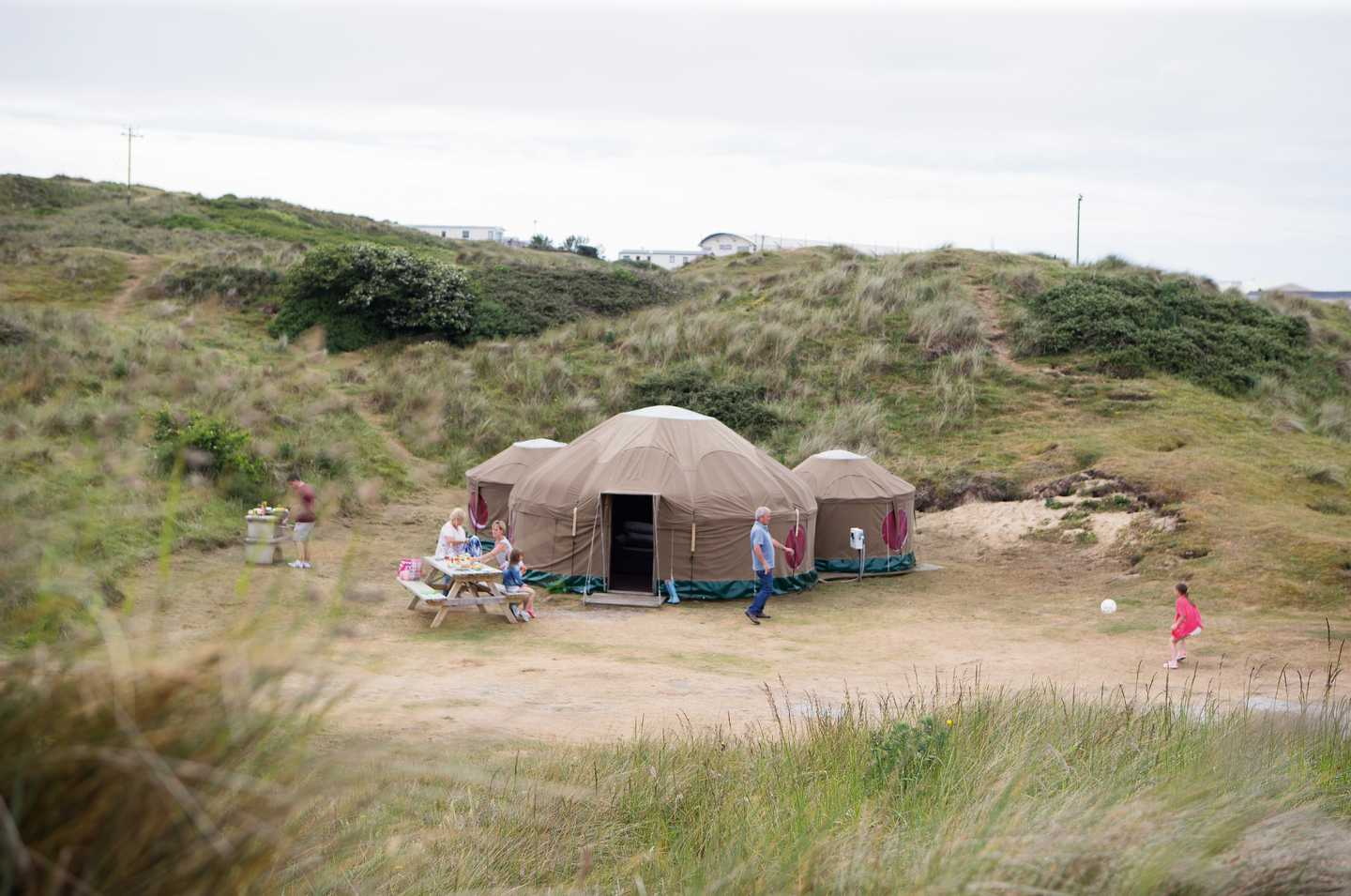 A family playing and having lunch outside their Yurt