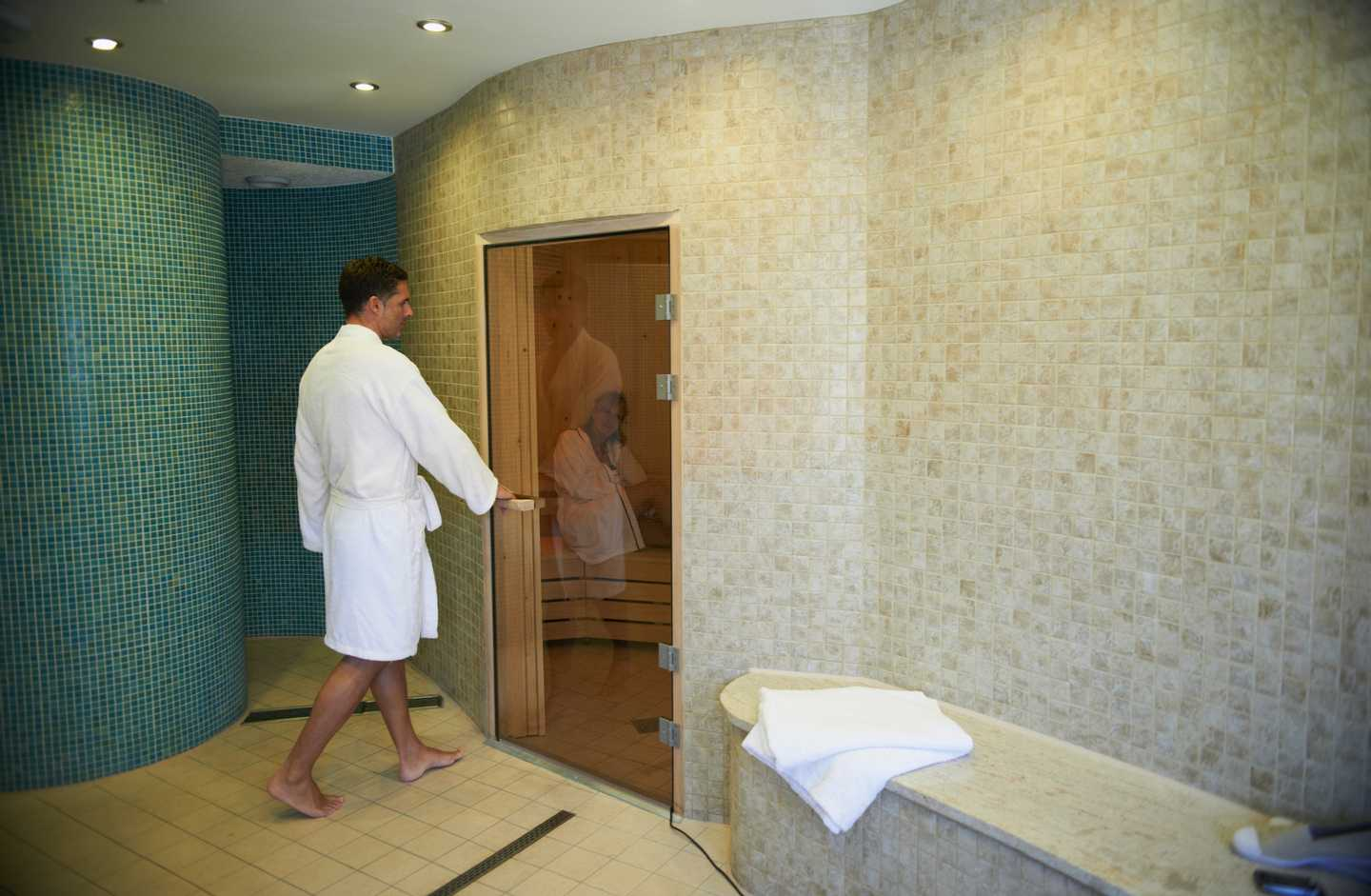A man in a white bathrobe opening the door to our sauna