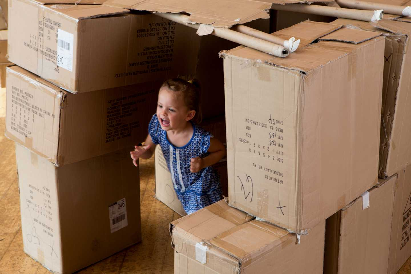 Child peeking out of pile of boxes