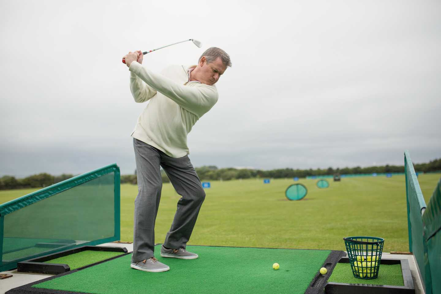 An owner practising his swing on the driving range at Far Grange