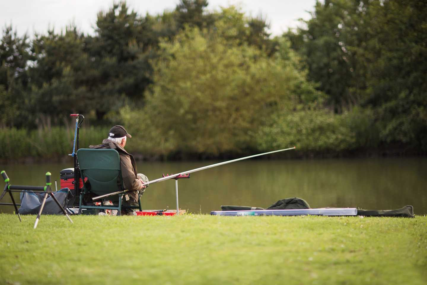 A man reclining in his chair as he waits for a fish to bite