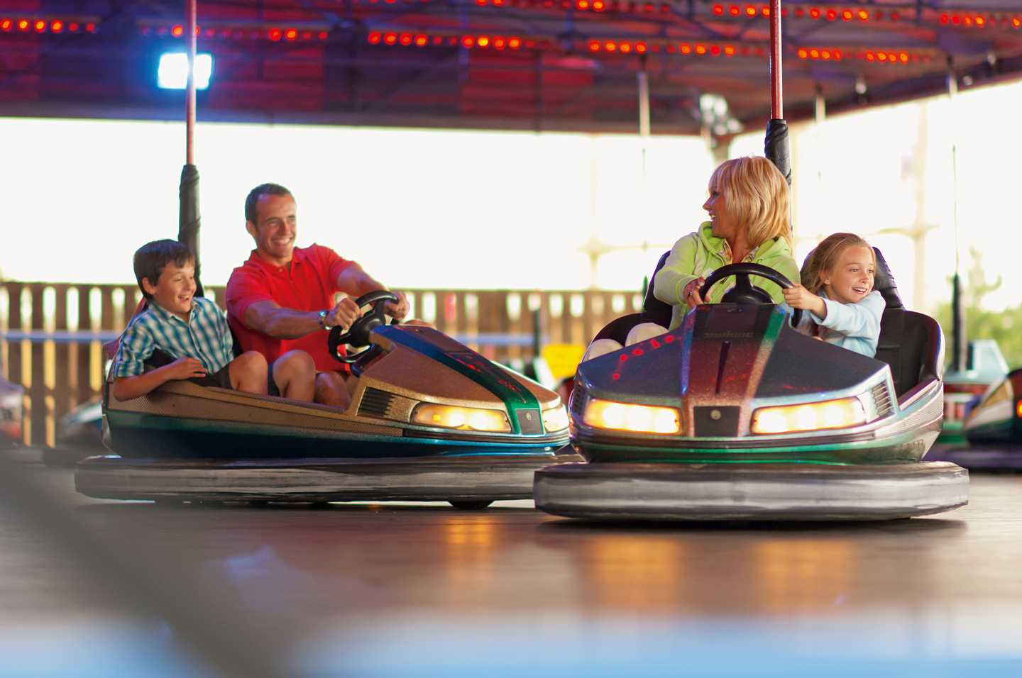 Family bumping into each other on the Dodgems at the funfair