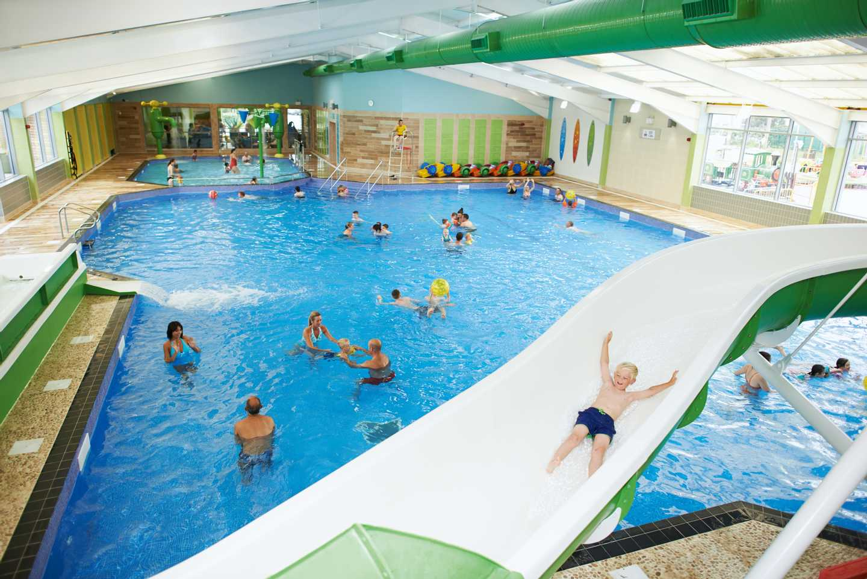 A child sliding down the indoor pool slide
