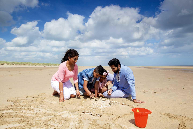Family creating a sand sculpture on beach