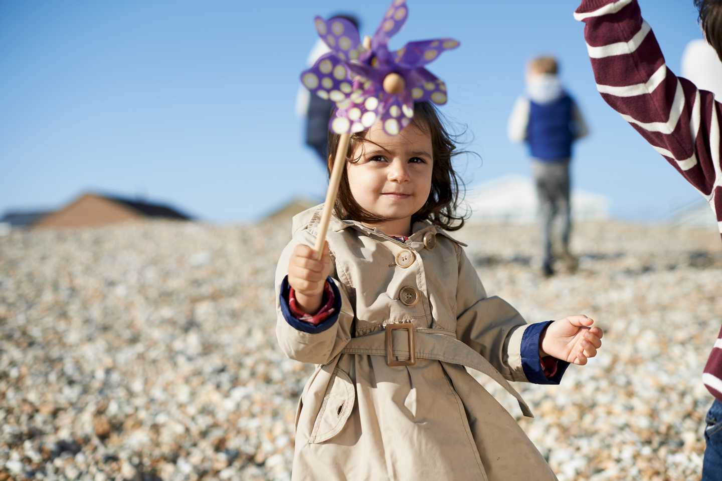 A little girl on the beach with a flower whirly windmill