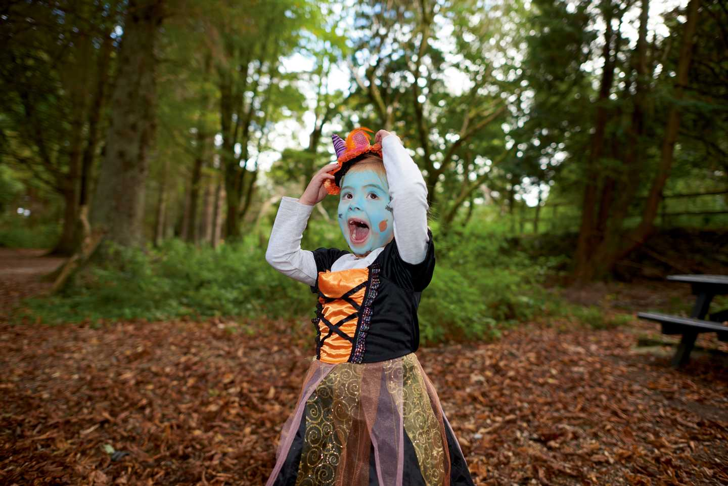 A girl dressed up for Halloween playing in the woods