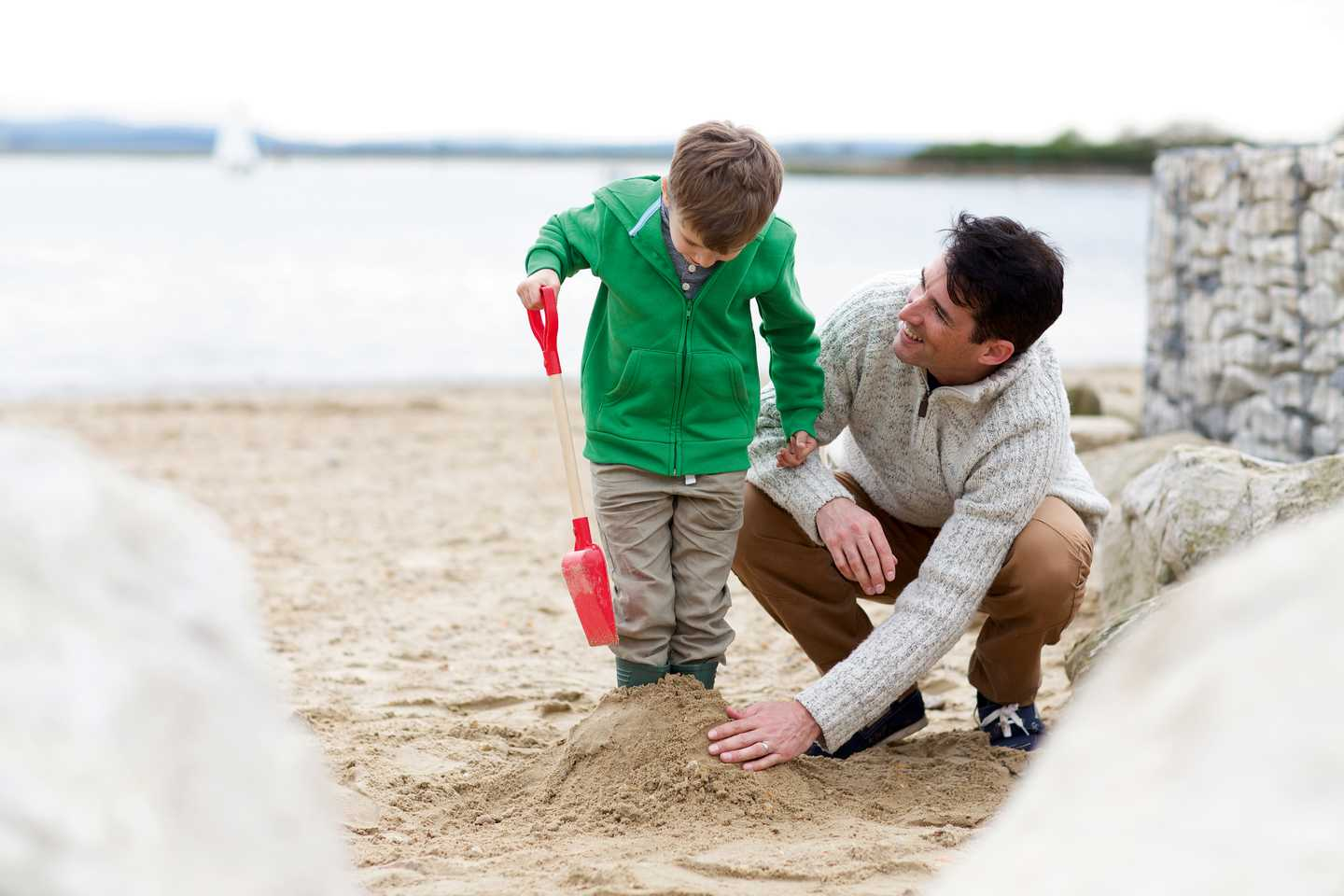 A father and son building sandcastles on the beach