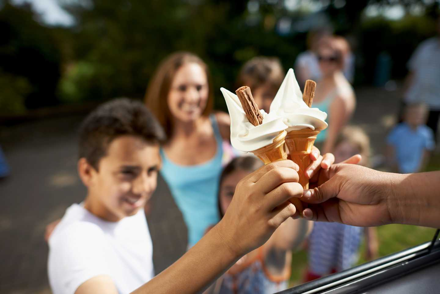 Happy family saying cheers with an ice cream
