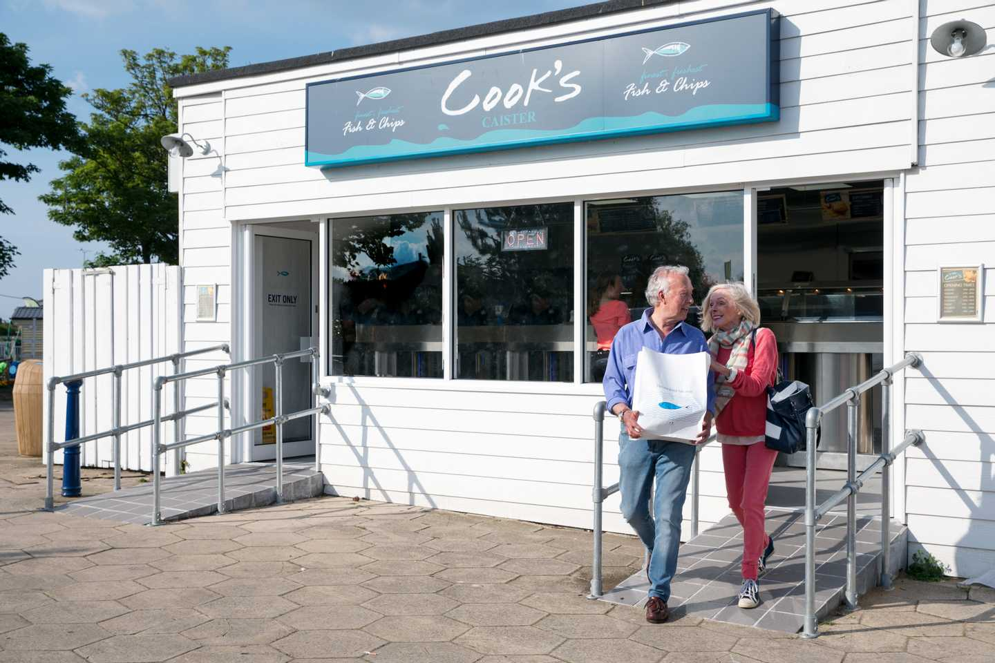 Elderly couple coming out of Cook's fish and chips with their dinner