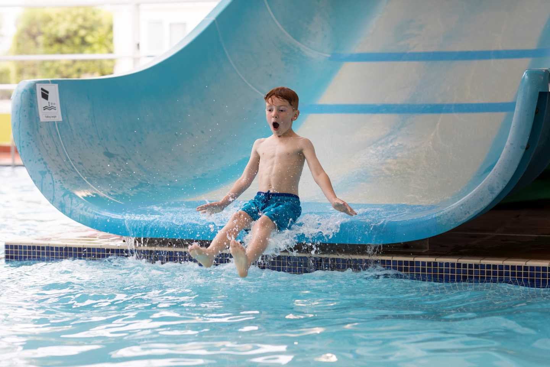 A boy sliding down the indoor pool slide