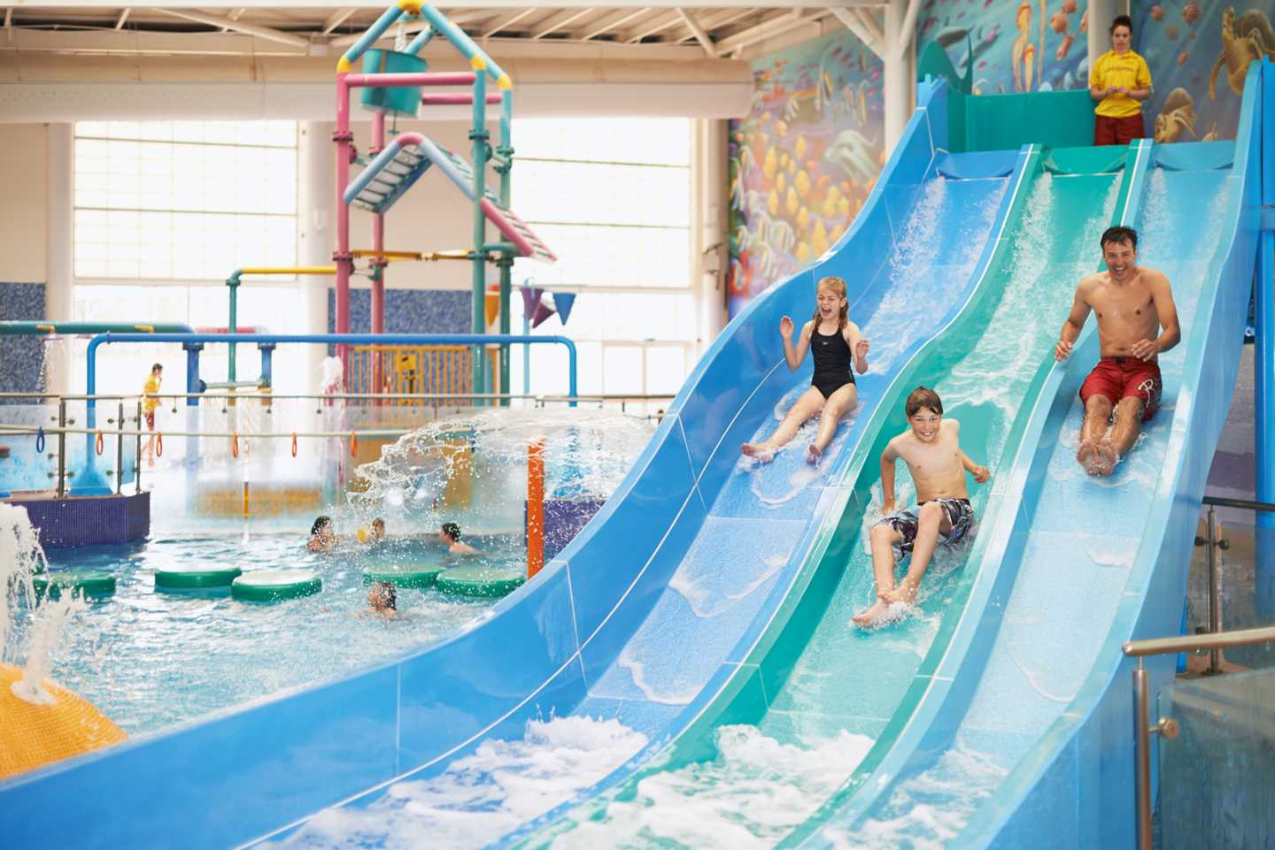 Children sliding down the indoor pool slide