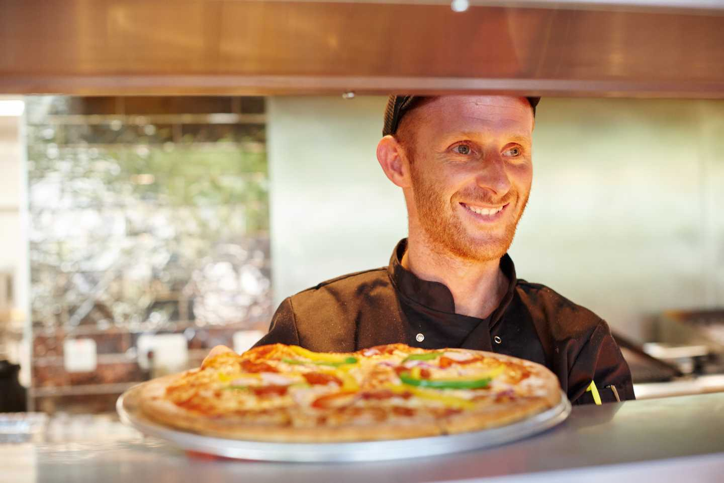 A chef has just finished cooking a pizza