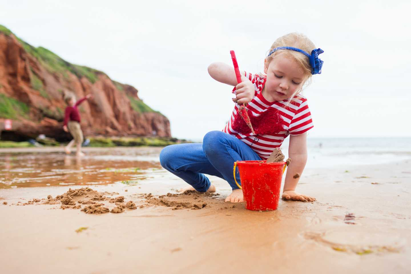 A toddler making sandcastles on the beach at Devon Cliffs