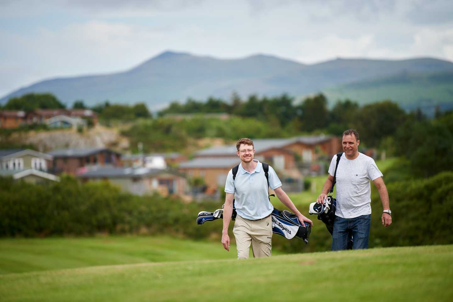 2 men carrying their golf bags along the 9-hole golf course with mountain in the background