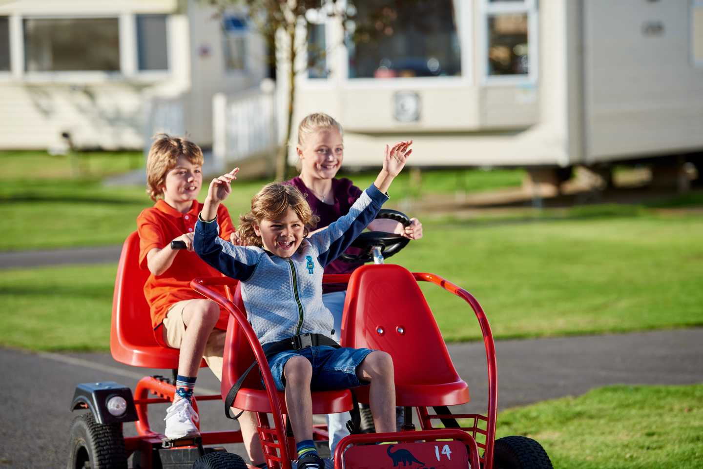 Children riding around the park in a hired kart