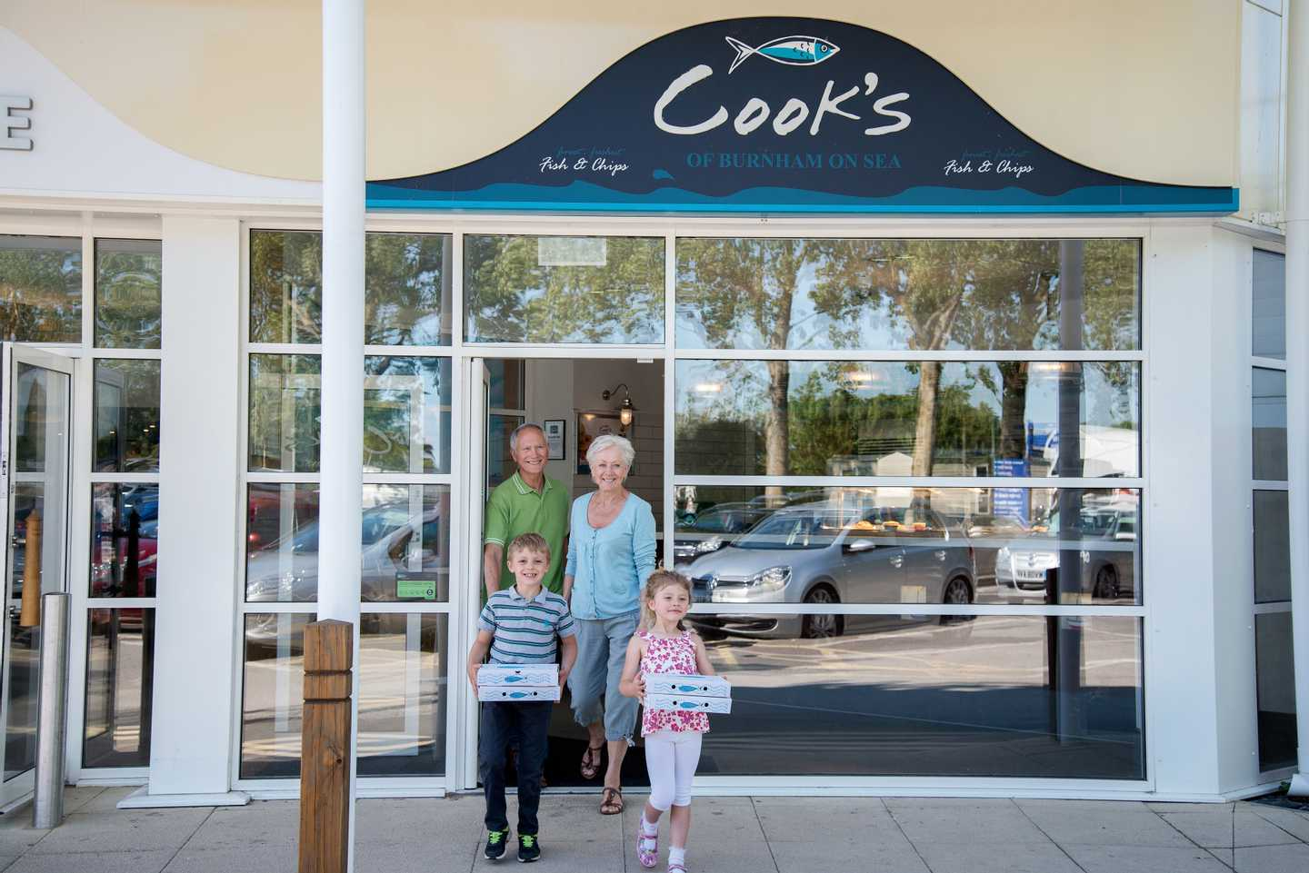 Family leaving Cook's fish and chips with their takeaway