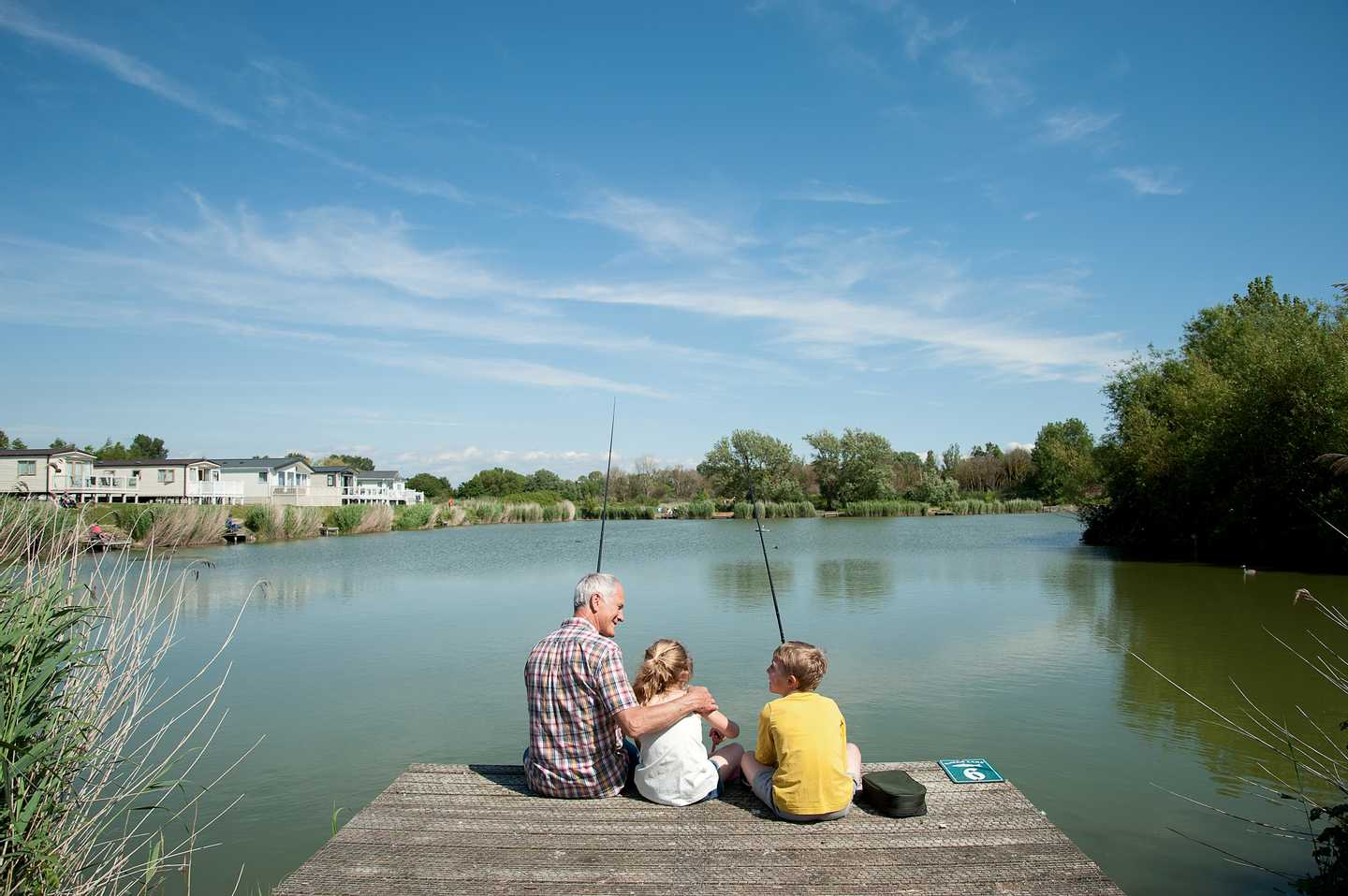 A man and two children perched on the side of a large lake with fishing rods on a sunny day