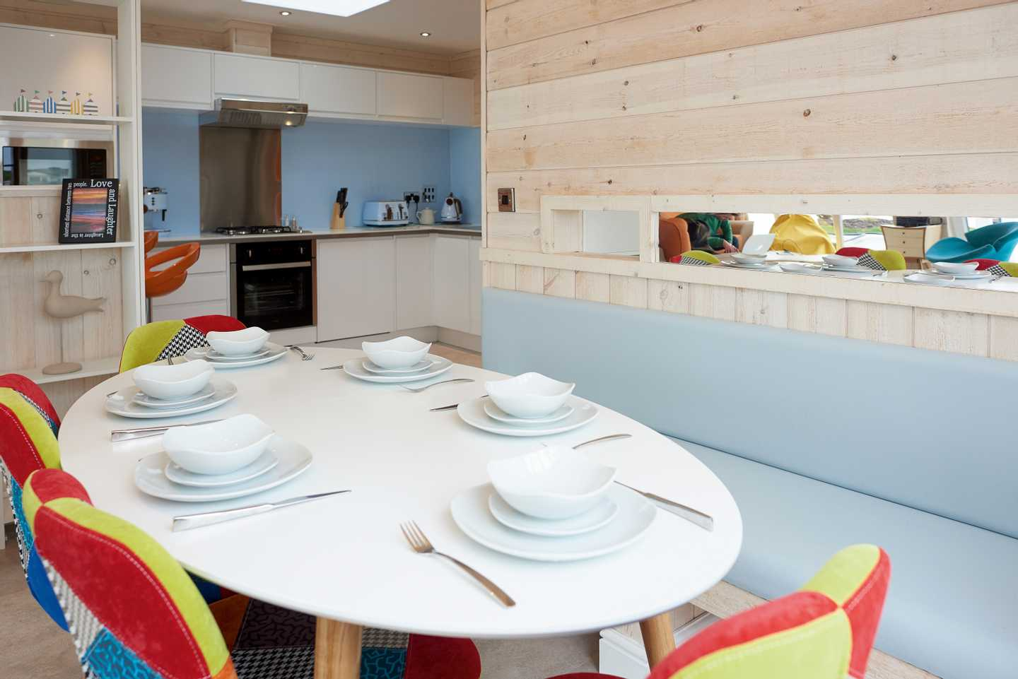 A Beach House dining table with plates, cutlery, chairs and other kitchen accessories