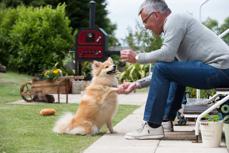 A man giving his dog a treat outside his caravan
