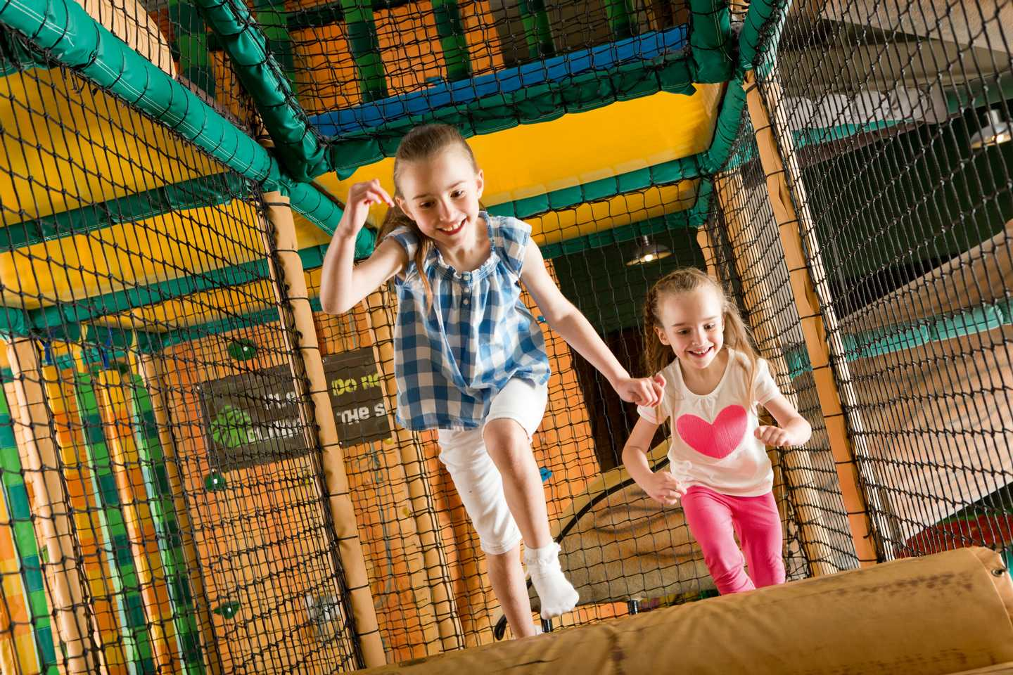 Girls climbing in the indoor play area