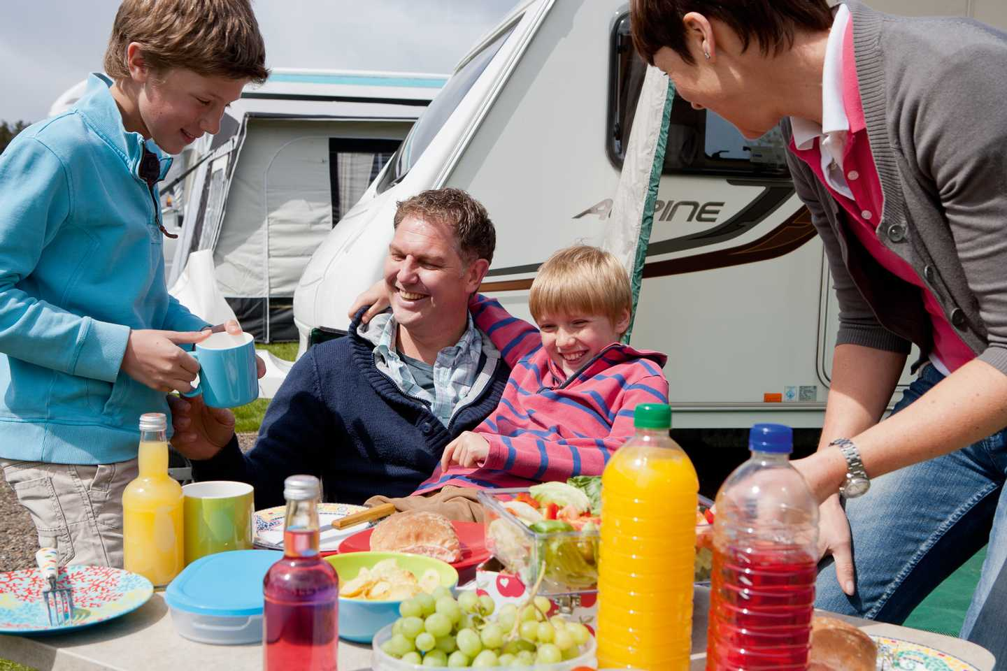 A family enjoying a picnic outside their caravan