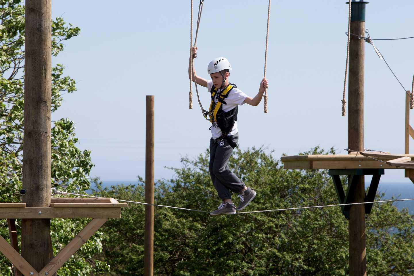 A guest on the Aerial Adventure ropes course at Devon Cliffs