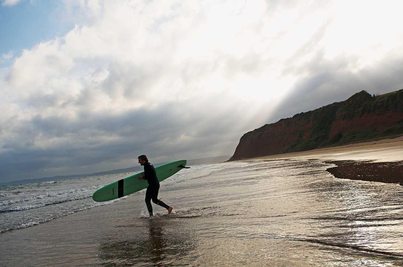 Devon surfer on the beach at sunset
