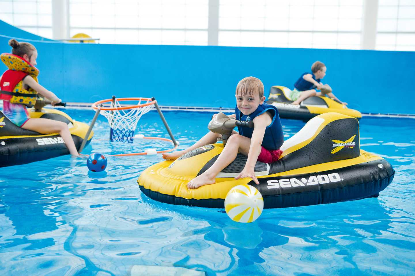 Child navigating the pool in an aqua glider