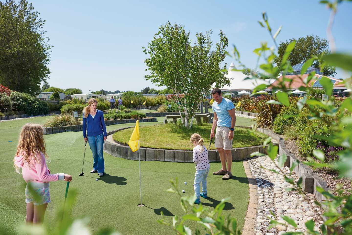 Family playing on the adventure golf course at Hopton Holiday Village