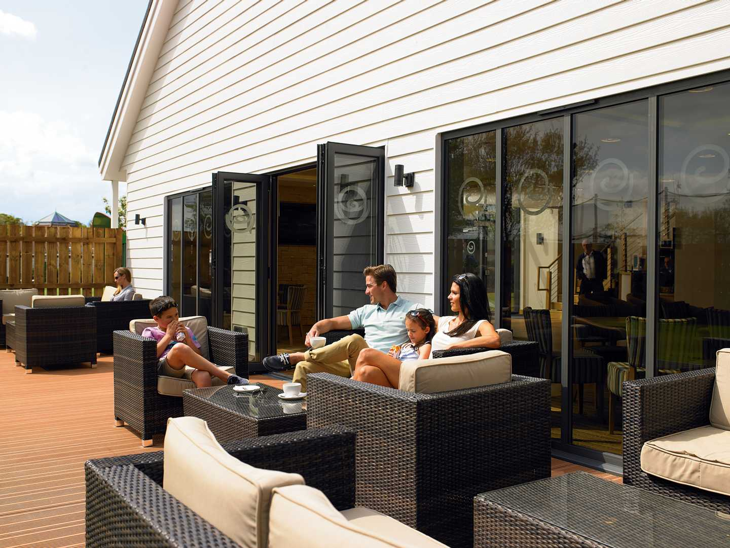 A family sitting on the decking area of the Owners' Lounge at Hopton