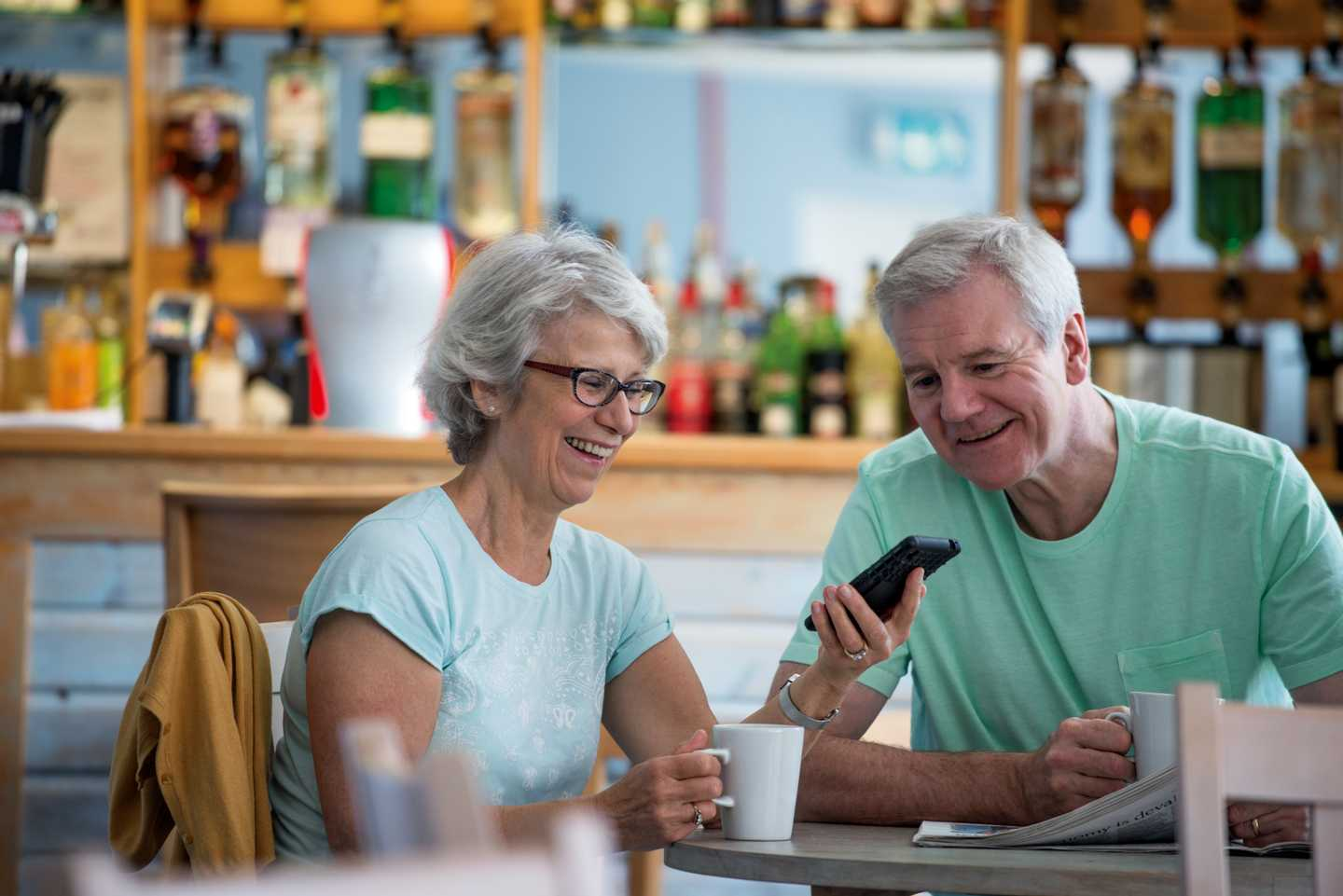 An older couple laughing at their phone whilst drinking coffee in The Pier Owners' Lounge