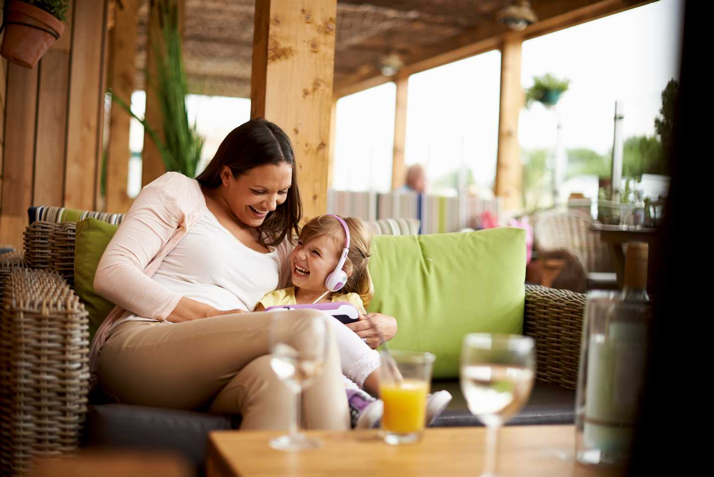 A mum and daughter relaxing with a drink in The Boathouse bar and restaurant whilst playing with one of the daughters toys