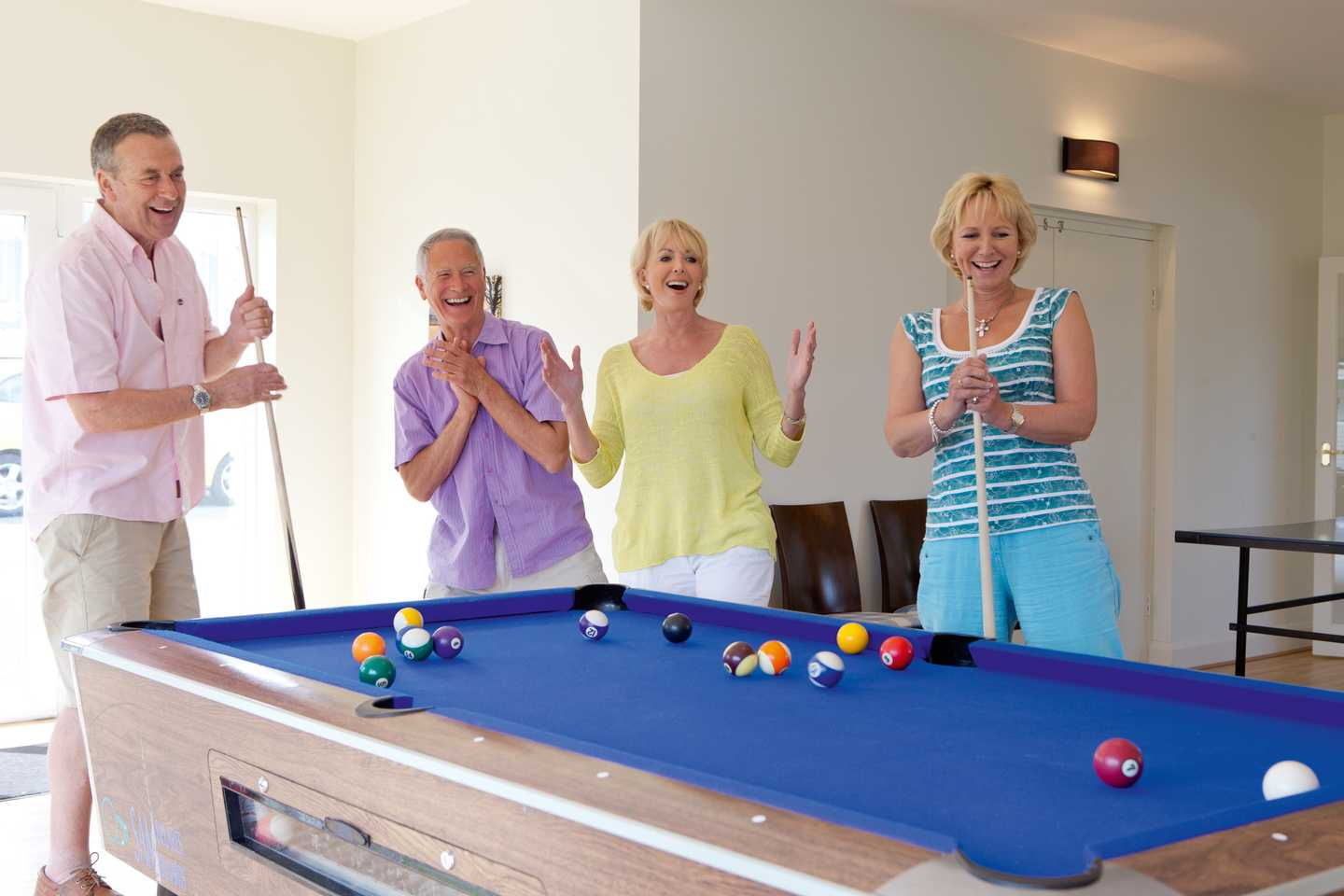 A group of friends having a game of pool in our Owners' Lounge