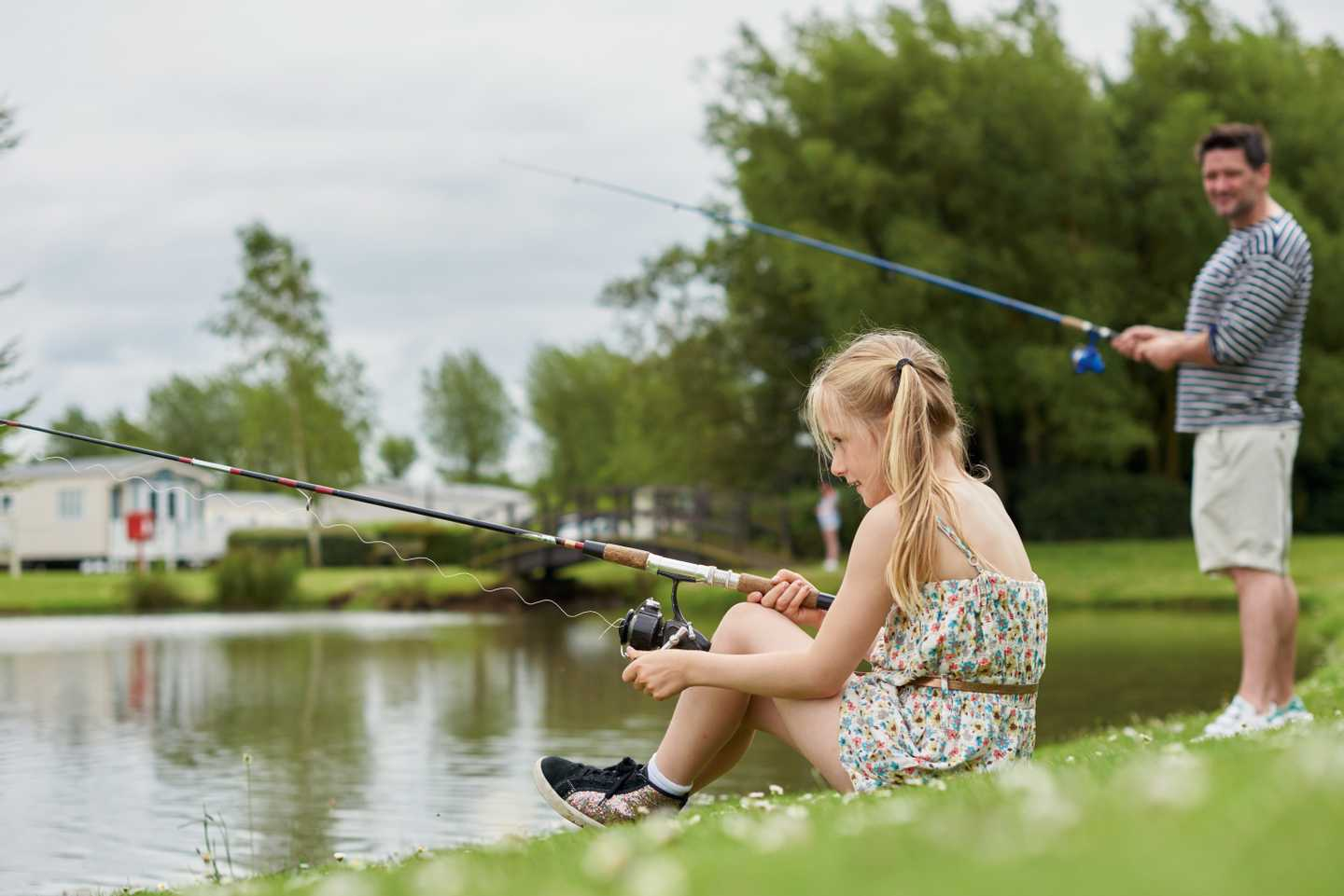 A father and daughter fishing by the lake