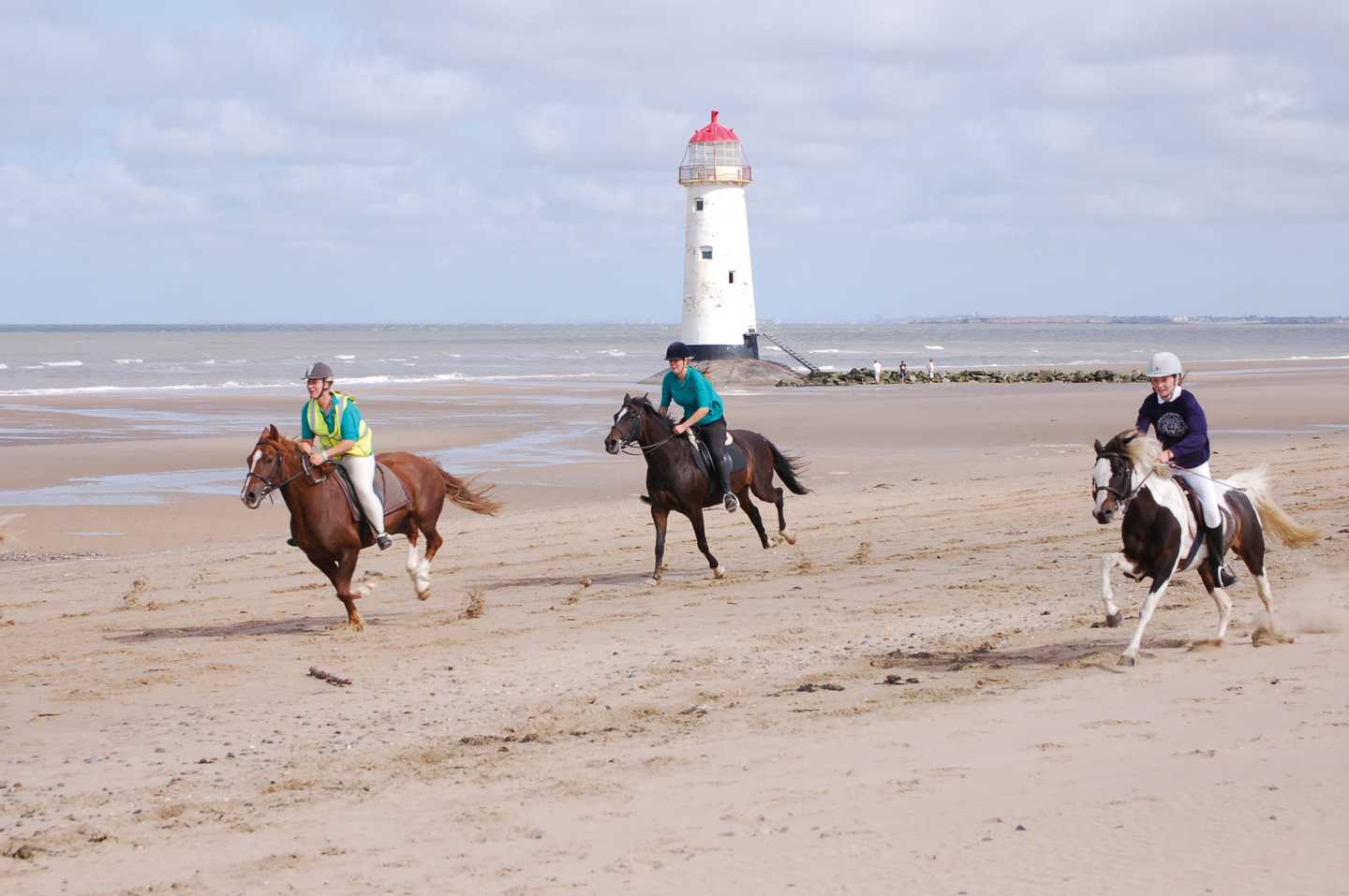 Three horses ridding along the beach with lighthouse in the background
