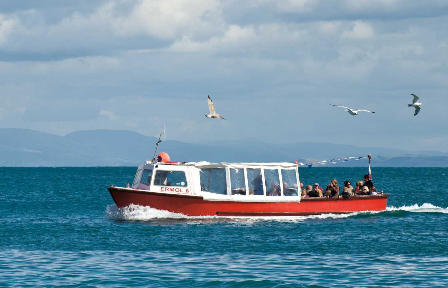 Red and white boat at sea with birds overhead