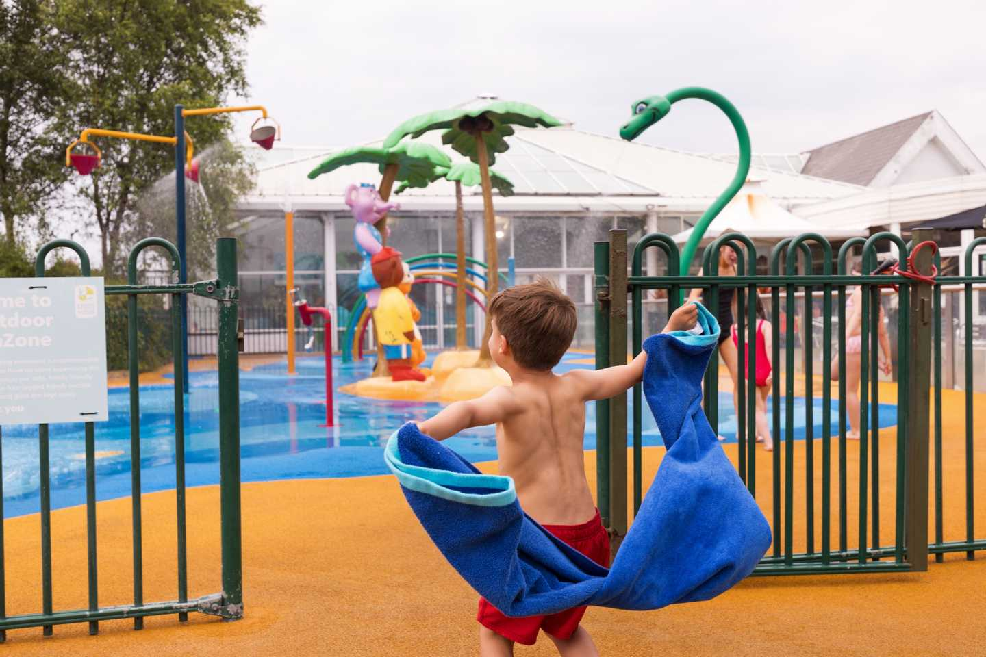 A child running towards the SplashZone with a towel