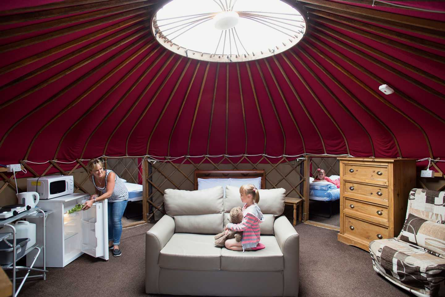 A family in a Yurt with a fridge, microwave, sofa and bedrooms
