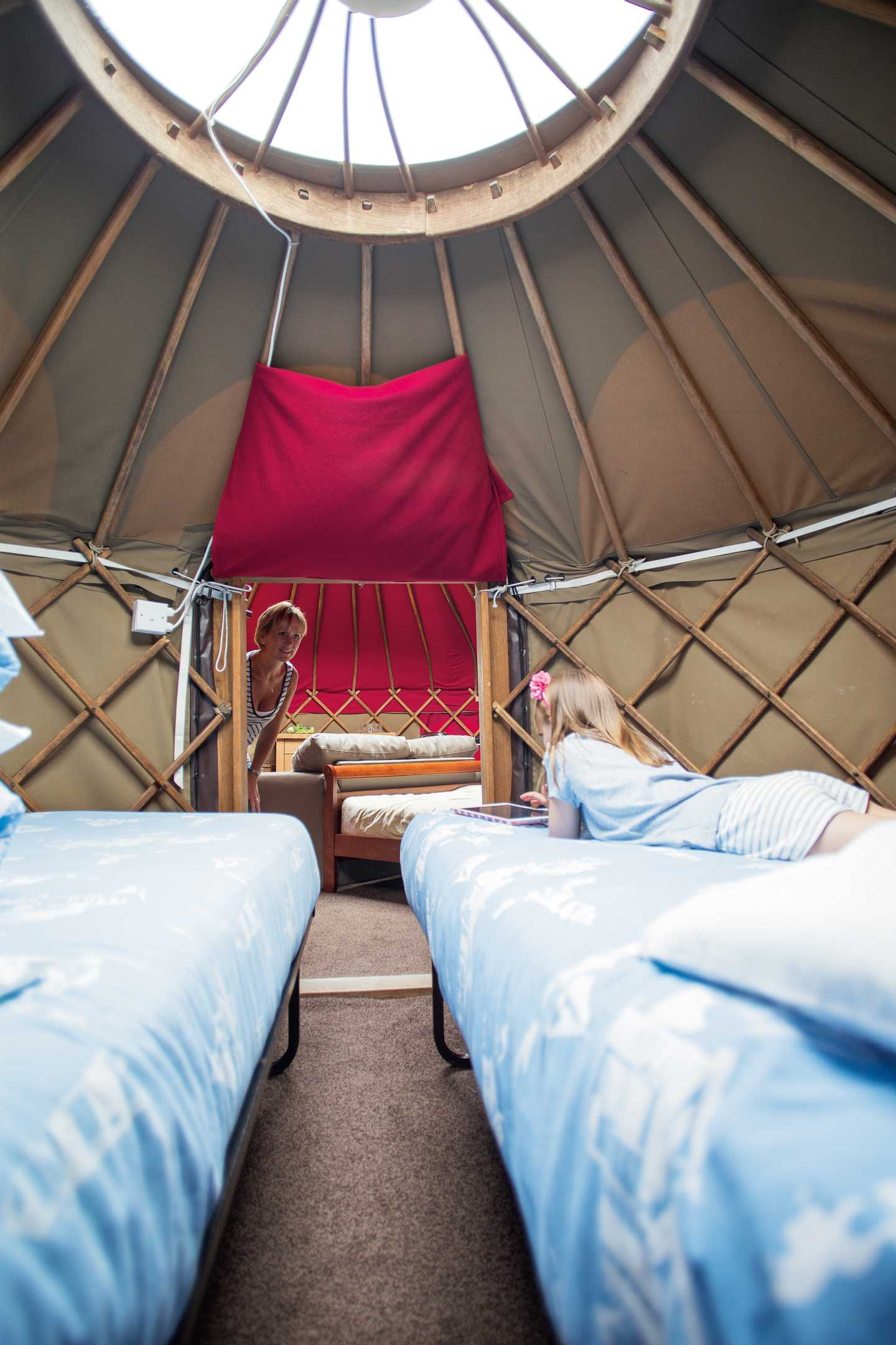 A girl laying down on a bed in a Yurt (exclusive to Perran Sands)