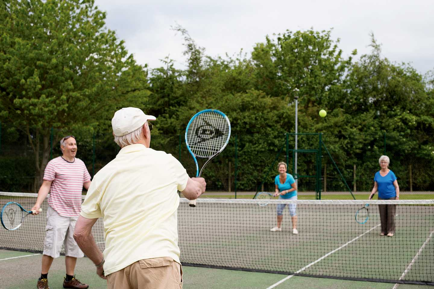 Friends playing a game of tennis doubles on the tennis court