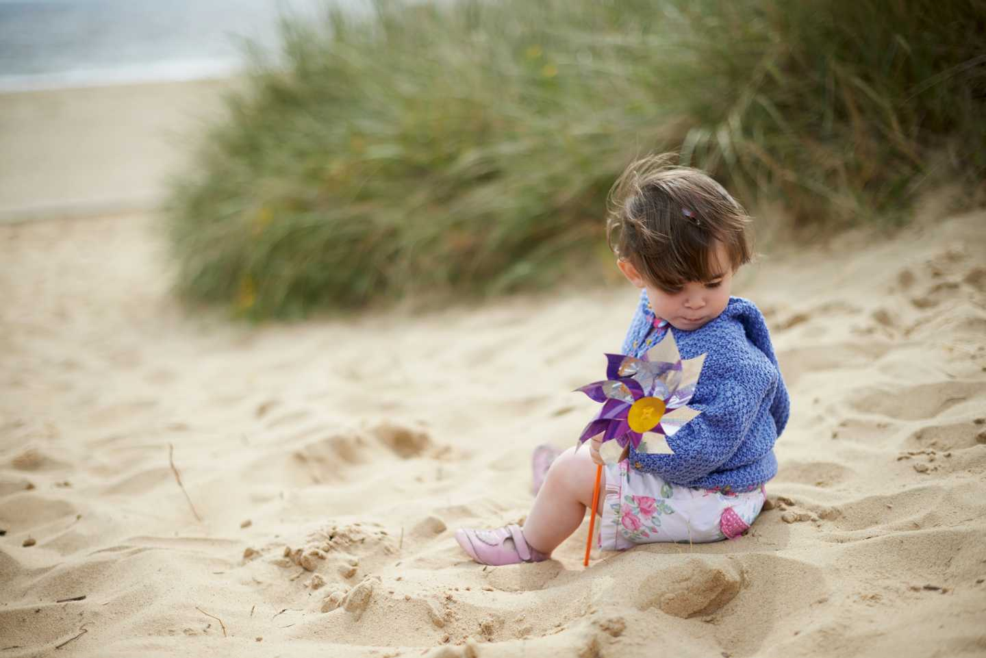 A young girl sitting in the middle of sand dunes as she looks around